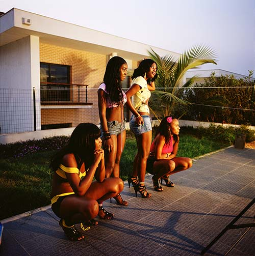 Angola, Four scantily dressed women watch on during the production of a Kuduru/Kuduro music video being shot at a private villa on the outskirts of Luanda that is worth in the region of USD 6,000,000. © Alfredo D'Amato / Panos Pictures