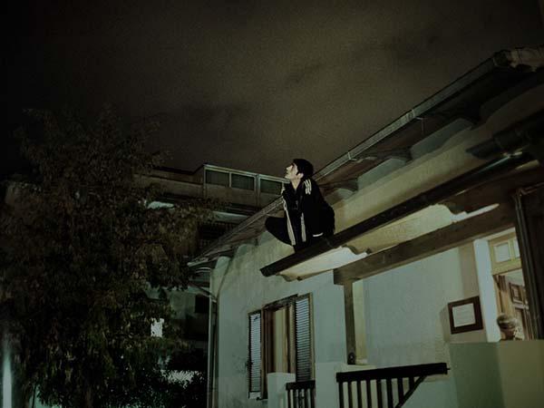 © Alvaro Deprit. Alem, un ragazzo della casa famiglia, sopra il tetto della casa. Da Suspension