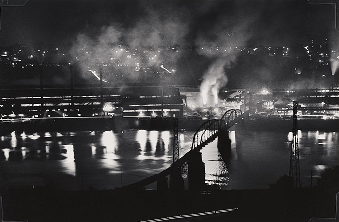 W. Eugene Smith, USA, 1918-1978. Stabilimento National Tube Company, U.S. Steel Corporation, McKeesport, e ponte ferroviario sul fiume Monongahela, 1955-1957. Stampa ai sali d'argento / gelatin silver print, 22.86 x 34.29 cm. Carnegie Museum of Art, Pittsburgh. Gift of the Carnegie Library of Pittsburgh, Lorant Collection.. © W. Eugene Smith / Magnum Photos