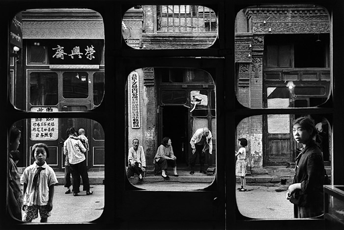 © Marc Riboud. Beijing, 1965. . Da Sha La street in old Bejing, as seen through an antique dealer's window. Private citizens come here to sell family jewels or other objects. The prices are fixed by the government.